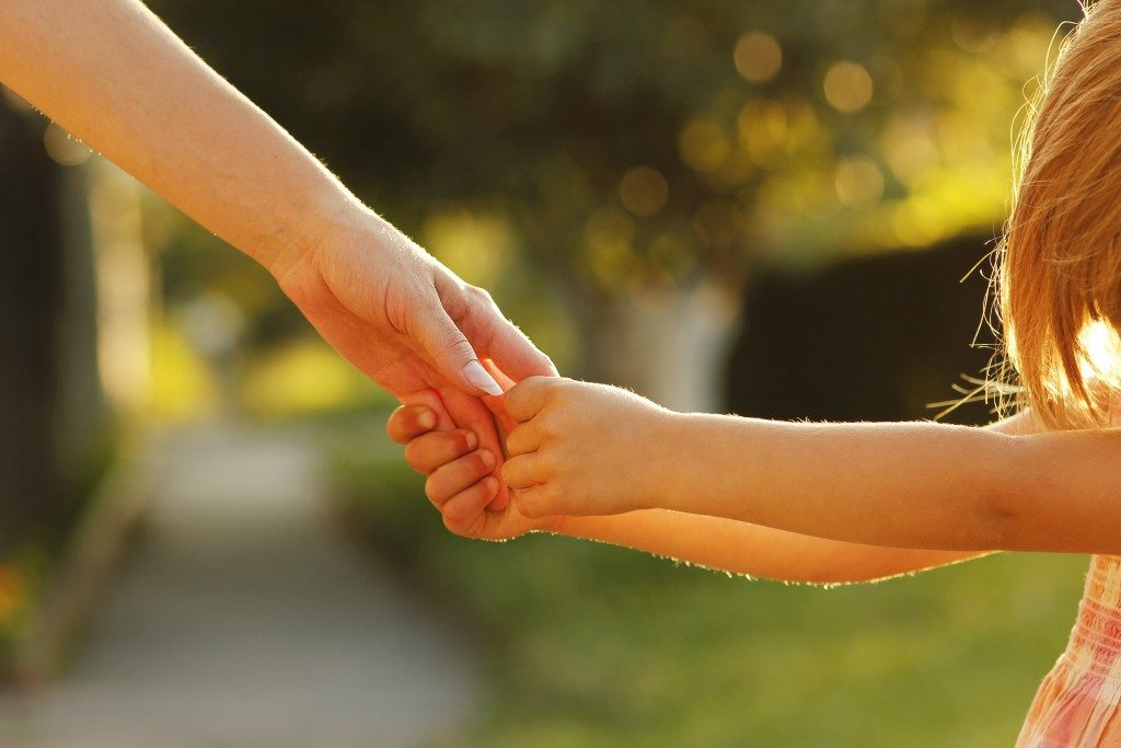 a child holding their parent's hand