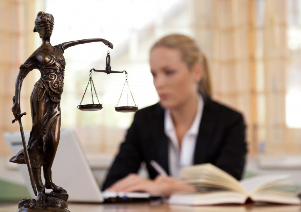 Photo of lady justice with court reporter behind