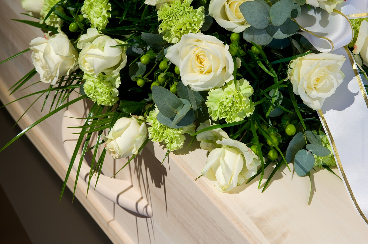 Coffin with white roses